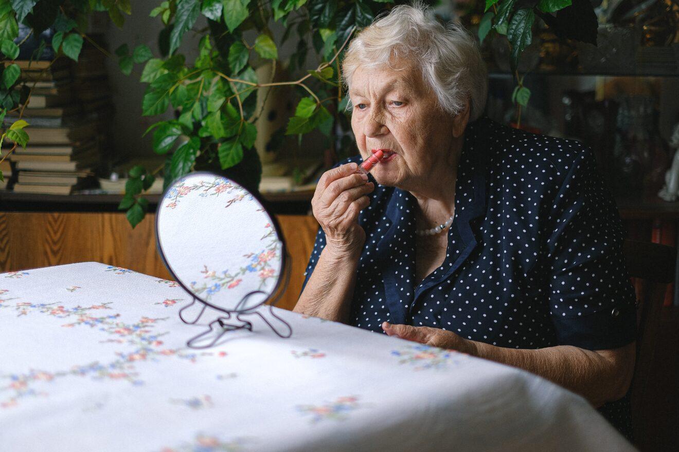 Oude dame doet lippenbalsem op