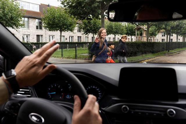 automobilist steekt zijn hand op naar voetgangers