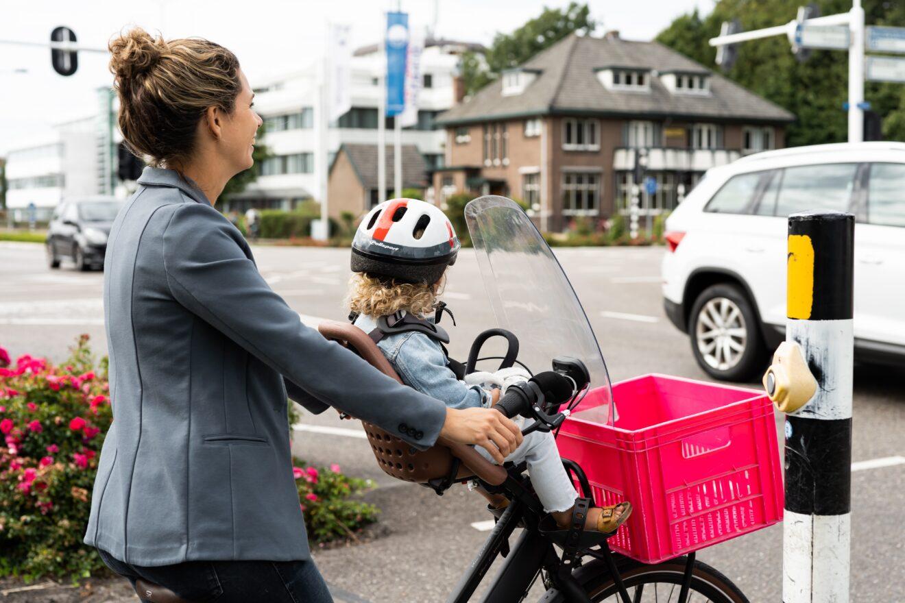 Wachtende vrouw met fiets en kind bij stoplicht