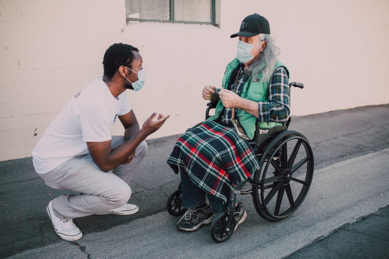 man praat tegen oudere man in rolstoel
