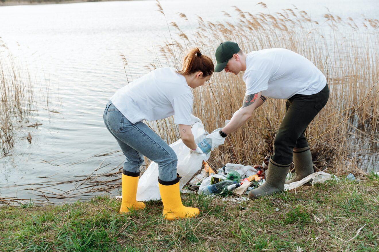 man en vrouw ruimen afval op aan de waterkant